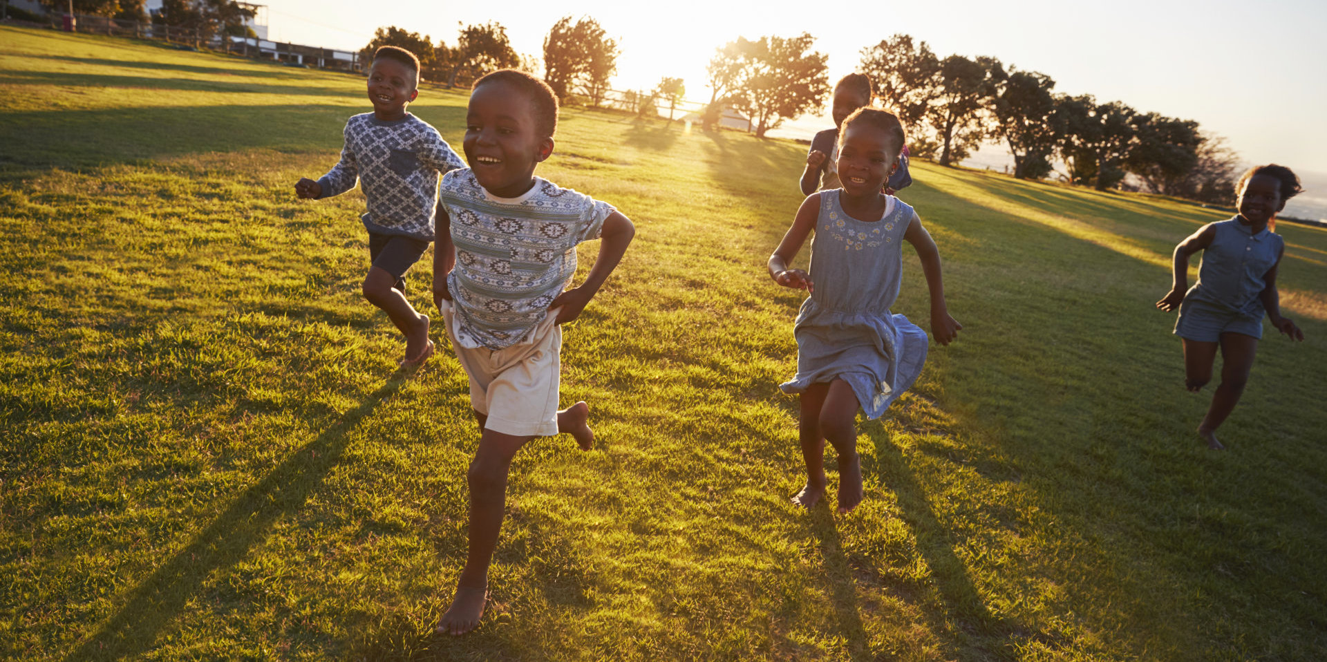 group of children playing under the sunset